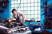 Young strong car mechanic at work in shop