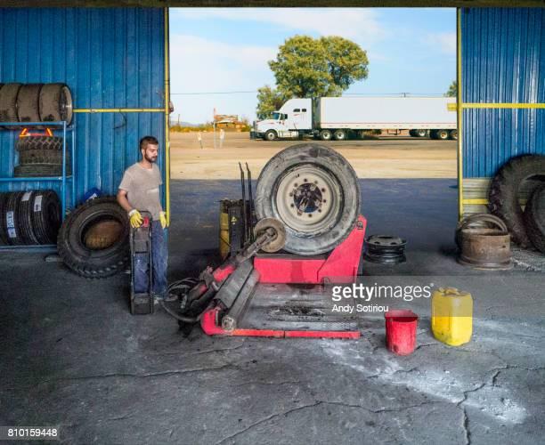 Car mechanic changing a truck tyre