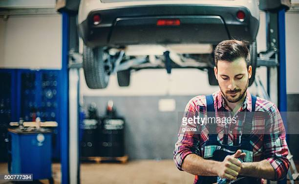 Car mechanic cleaning his hands after work.