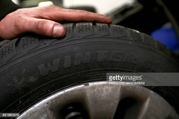 A car mechanic holds a winter tire at a garage in Reims northeastern France on January 18 as a cold snap sweeps across Europe / AFP / FRANCOIS...