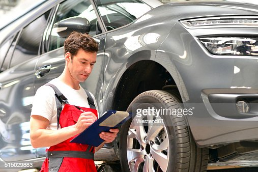 Car mechanic in a workshop holding clipboard