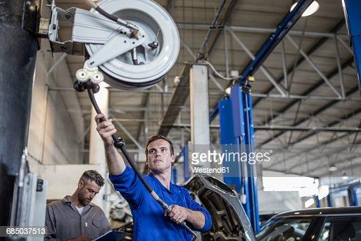 Car Mechanic In A Workshop Pulling On Hose Machine Photo – Machine Mechanic