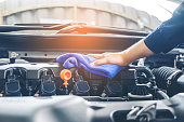 Car mechanic inspecting engine during service procedure