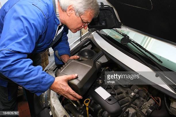 Car mechanic is changing engine oil