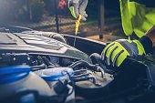 Car Mechanic Checking Oil Level in Modern Car Engine.