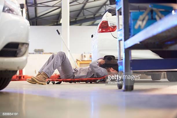 Car mechanic on creeper dolly at work in repair garage