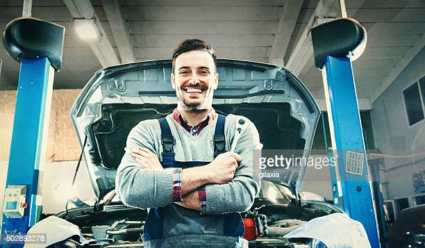 Car mechanic proudly posing.
