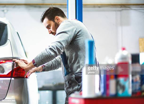Car mechanic replacing tail light on a vehicle.