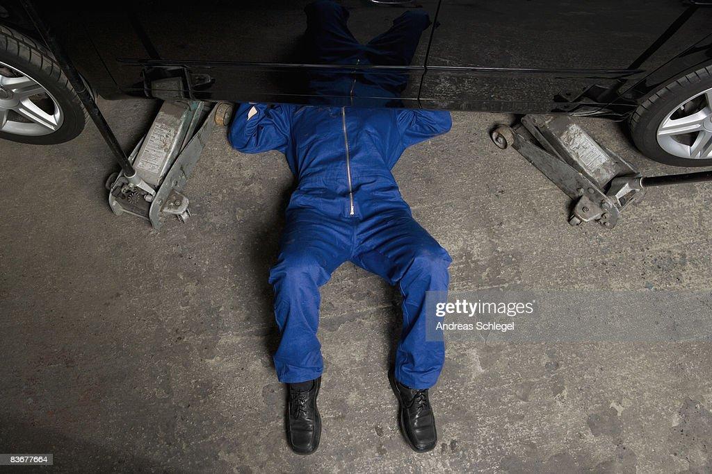 A car mechanic servicing a car