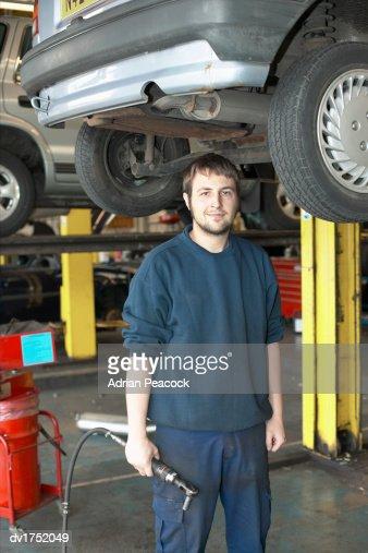 Car Mechanic Standing in a Repair Shop : Stock Photo