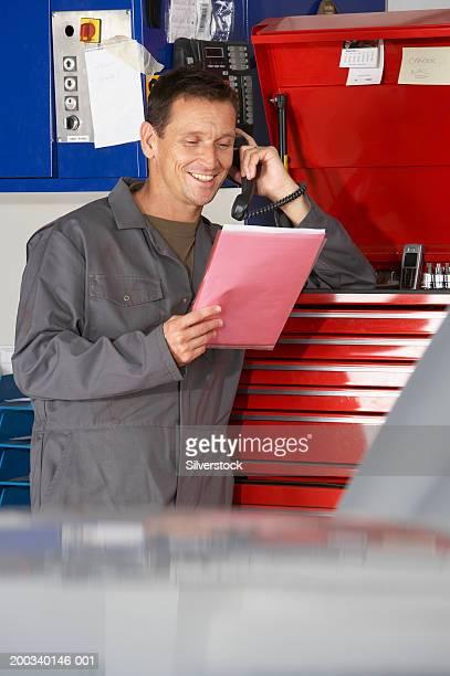 Car mechanic using telephone in garage, holding file, smiling