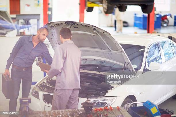 Car mechanic with client in repair garage