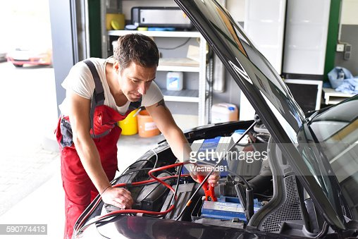 car mechanic working in repair garage reloading car battery stock photo getty images. Black Bedroom Furniture Sets. Home Design Ideas
