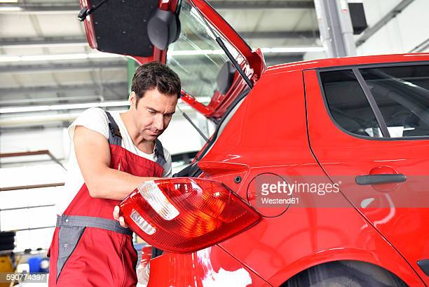 Car mechanic working in repair garage, repairing rear light