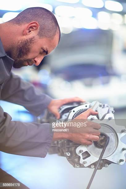 Car mechanic working on gearbox in repair garage
