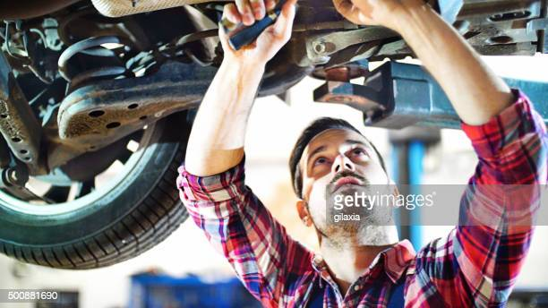 Car mechanic working under a vehicle at workshop.