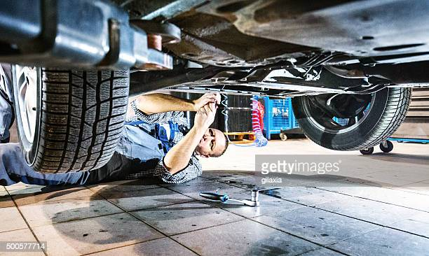 Car mechanic working under a vehicle.