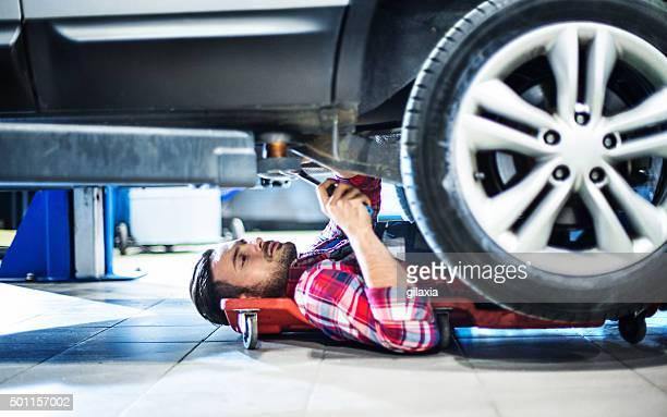 Mécanicien travaillant sous voiture, un véhicule.