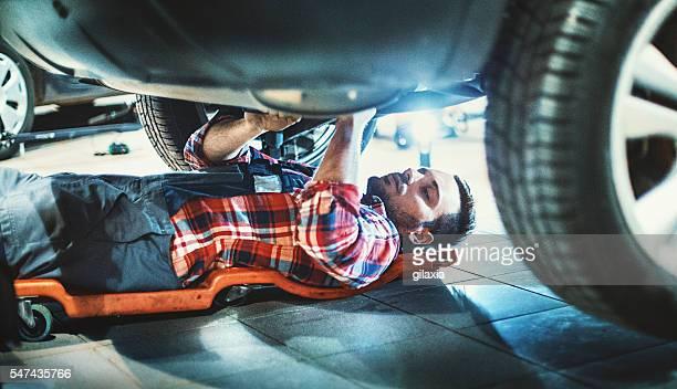 Car mechanic working under a vehicle.