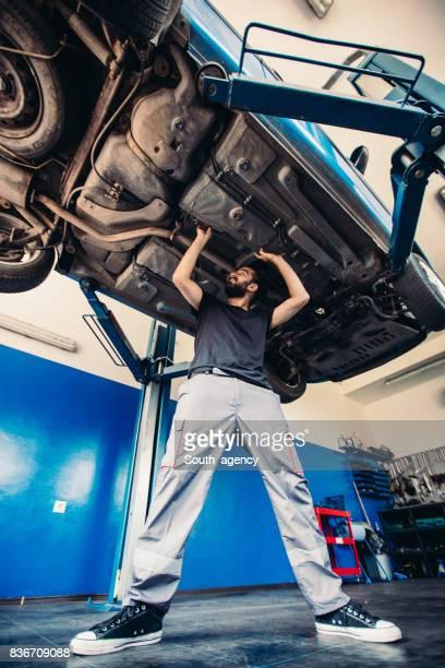Car mechanic working under a vehicle