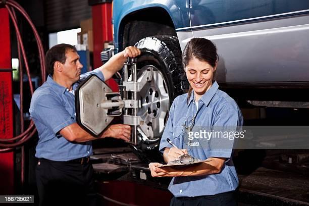 Car mechanics performing wheel alignment