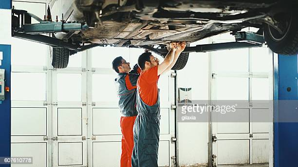 Car mechanics workin on low section of a sedan vehicle.