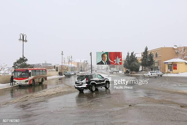 A car moving near the Heydar Aliyev's portret in a street during a snowstorm in Baku Azerbaijan