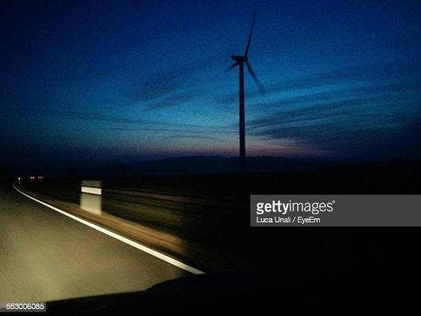 Car Moving On Road With Wind Turbine At Roadside
