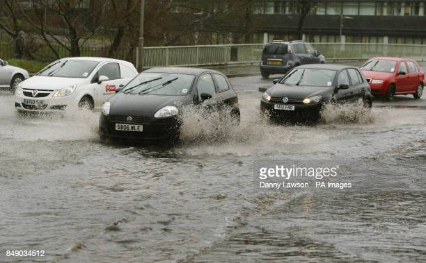 A car negotiates a flooded road in Paisley Scotland as torrential rain and high winds are expected across much of the country