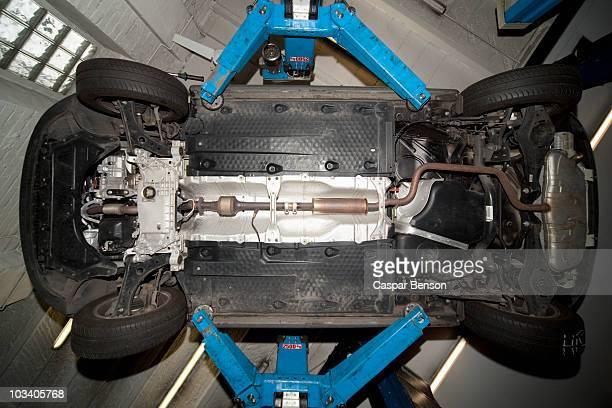 A car on a car lift in a auto repair shop
