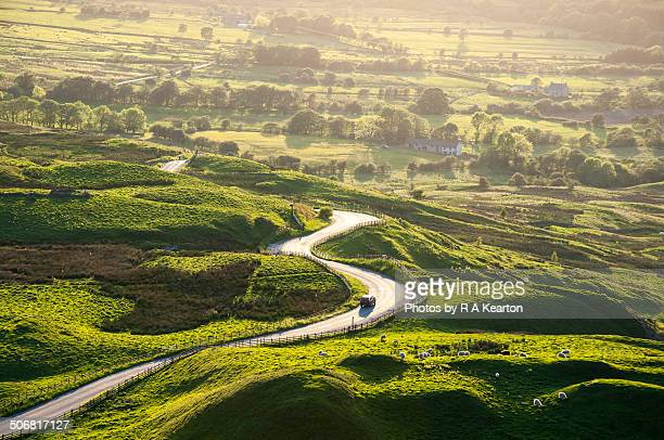 Car on bendy road through Peak District landscape
