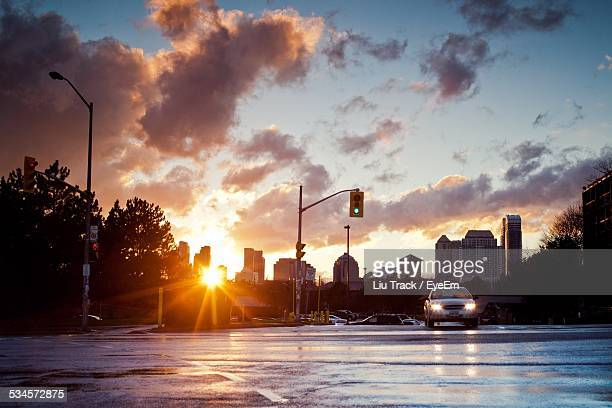 Car On City Street Against Cloudy Sky During Sunset