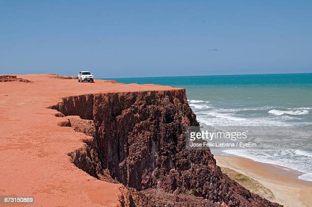 Car On Cliff By Sea Against Clear Blue Sky