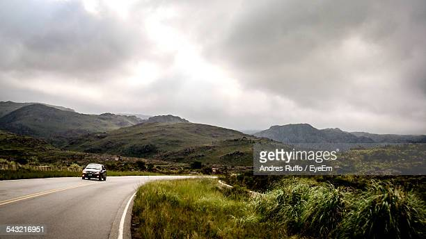 Car On Country Road Against Cloudy Sky
