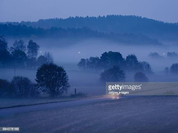 Car on country road at foggy evening
