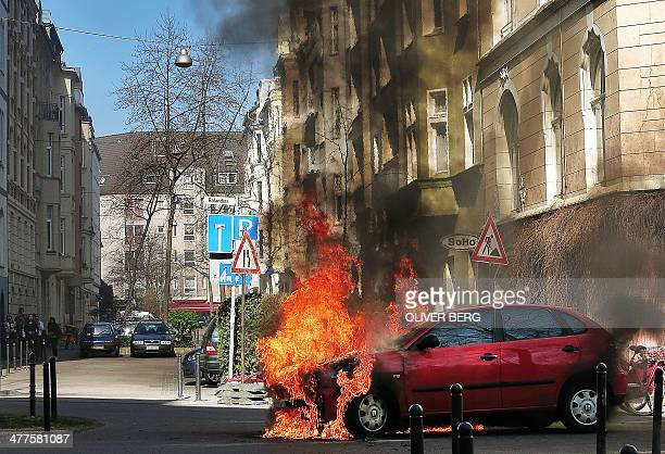 A car on fire stands on a street in Cologne western Germany on March 10 2013 The fire broke out due to a technical damage of the car as fire workers...