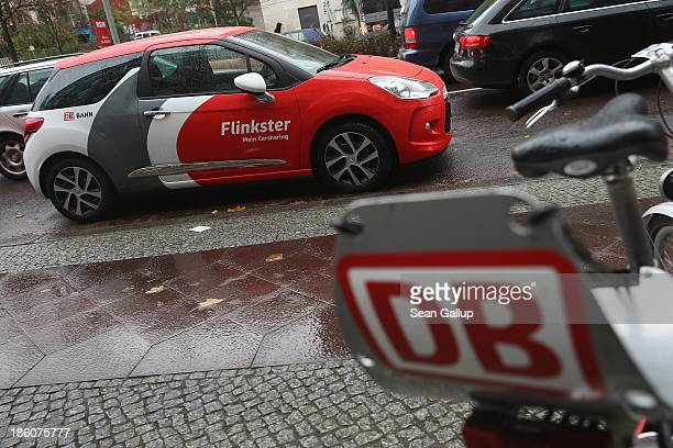 A car operated by the Flinkster carsharing company and rental bicycles operated by Deutsche Bahn stand parked on October 28 2013 in Berlin Germany...