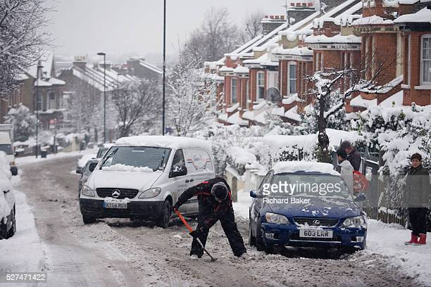 A car owner attempts to shovel his way out of snow on a hill in South London Bending down to remove the fallen snow from the road he will again try...