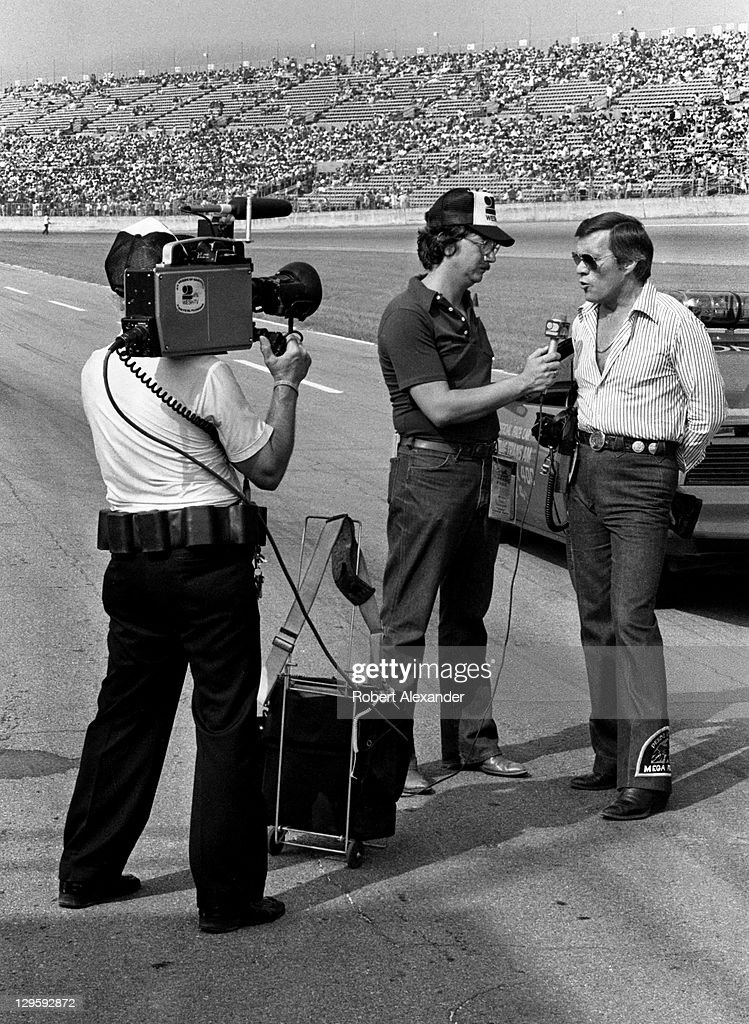 NASCAR car owner, film director and stuntman Hal Needham is interviewed by a Daytona Beach television reporter at the Daytona International Speedway prior to the start of the 1982 Firecracker 400 on July 4, 1982 in Daytona Beach, Florida. Needham owned the Skoal Bandit car driven by Harry Gant.