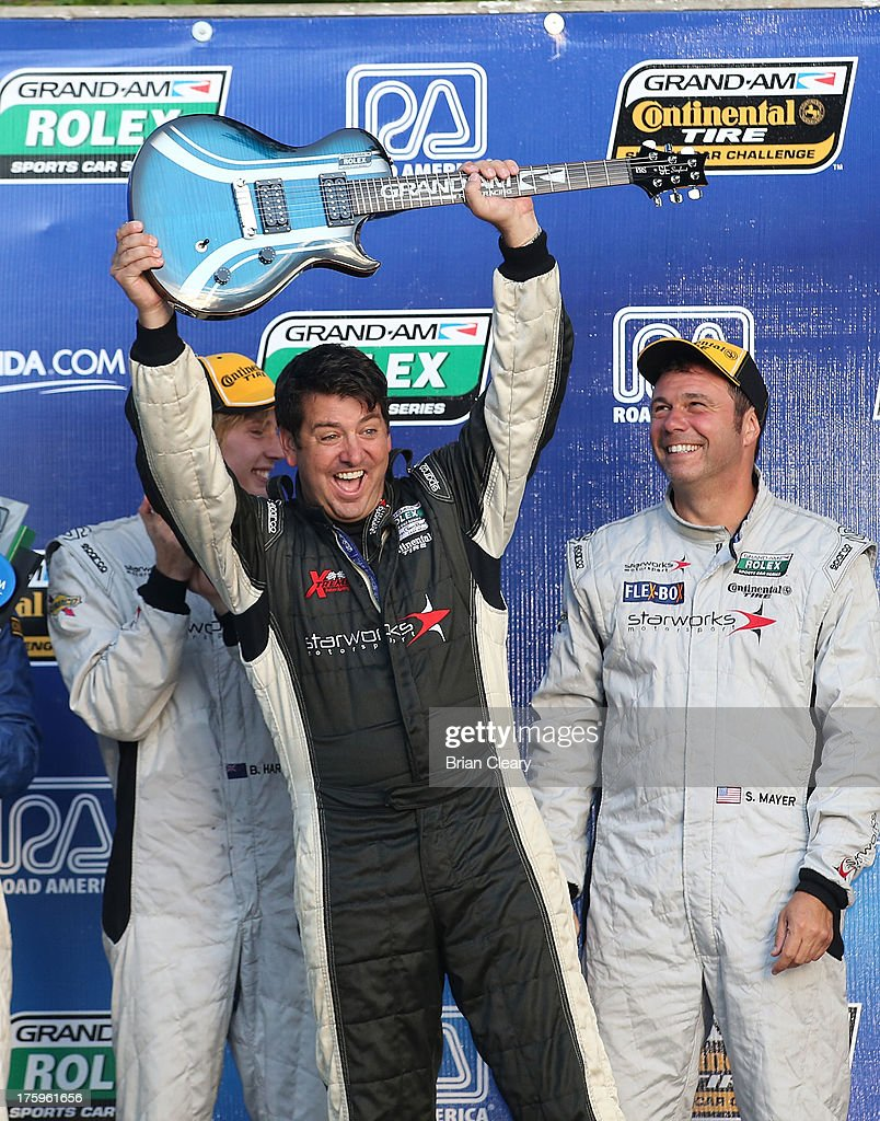 Car owner Peter Baron raises his victory guitar as his drivers look on after winning the VisitFlorida.com Sports Car 250 at Road America on August 10, 2013 in Elkhart Lake, Wisconsin.