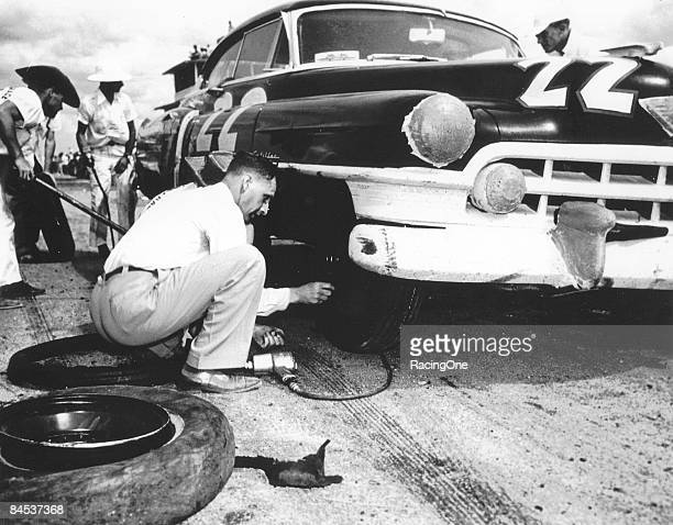 Car owner Raymond Parks affixes the lug nuts to his driver Red Byron's 1950 Cadillac They went on to finish third in the inaugural Southern 500 that...