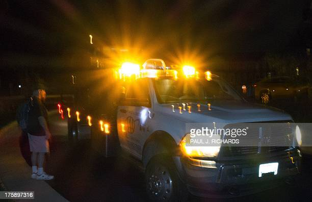 A car owner watches as a Triple A tow truck driver hooks up a broken down car on it's way to repair August 9 2013 in Centreville Virginia AFP...