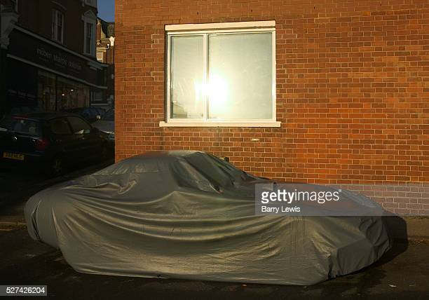 Car parked off road on a London street covered in protective wrapping to protect it against theft and bad weather