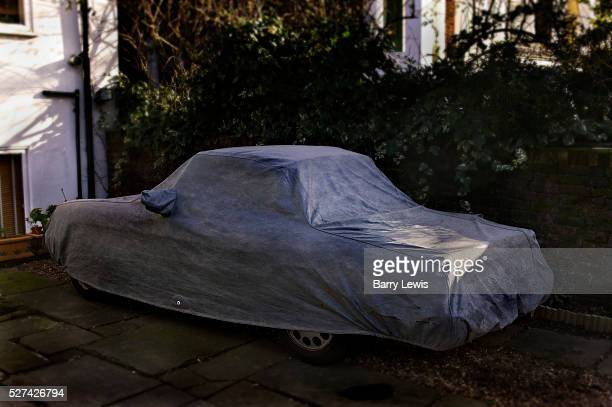 Car parked on a London street covered in protective wrapping to protect it against theft and bad weather while it is kept off road on a building's...