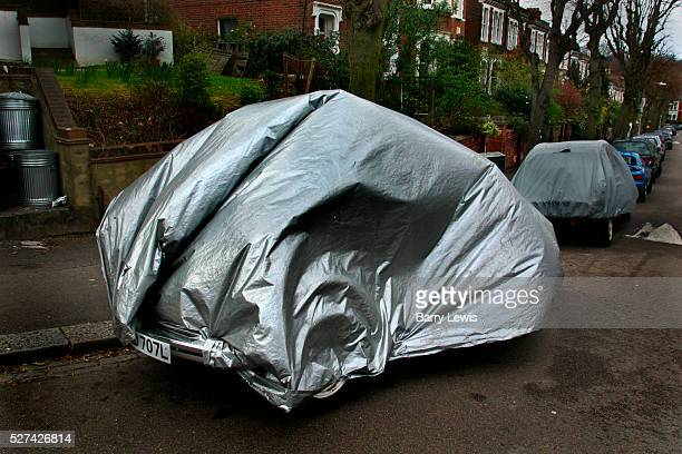 Car parked on a London street covered in protective wrapping to protect it against theft and bad weather Wind is blowing up the greysilver covering