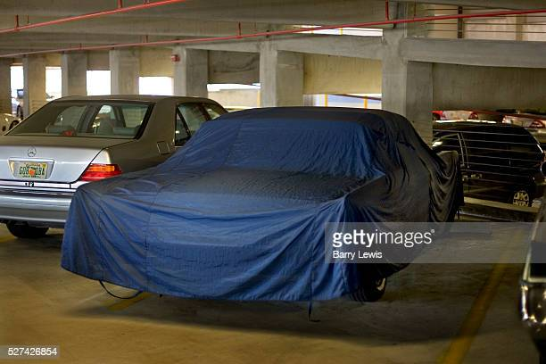 Car parked on a Miami indoor parking lot covered in blue protective wrapping to protect it against theft and bad weather