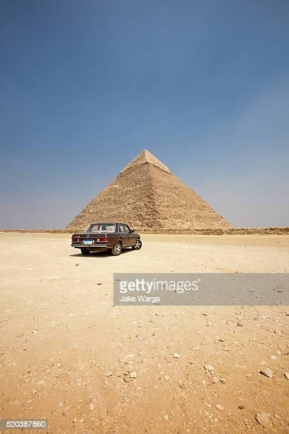 Car parkied next to pyramid, Giza, Egypt