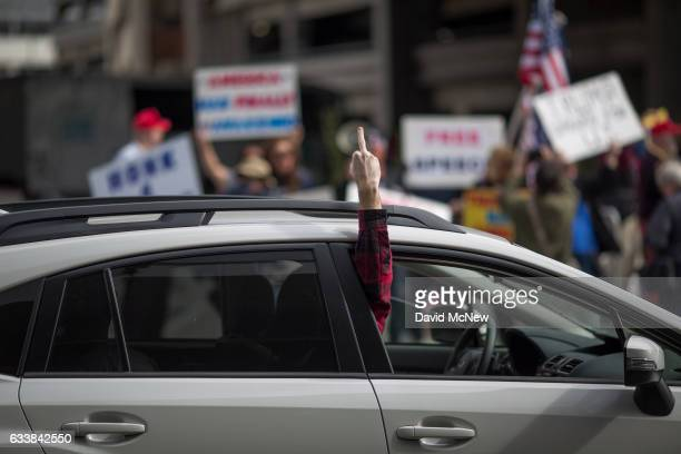 A car passenger makes an obscene gesture while passing Trump supporters demonstrating against a ruling by a federal judge in Seattle that grants a...