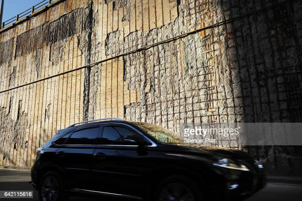 A car passes a chipped and damaged wall under a bridge in Brooklyn on February 16 2017 in New York City An annual report by the American Road and...