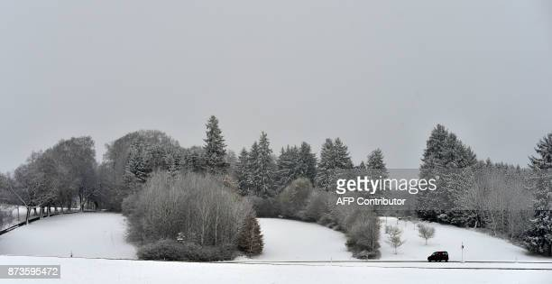 A car passes a country road in a snowy landscape near the village Marktoberdorf southern Germany after a first onset of winter in Bavaria with...
